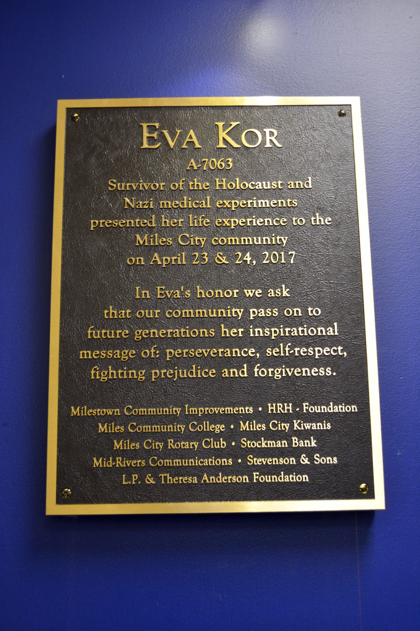 <strong>The plaque dedicated to Eve Kor hangs in the gym lobby at the high school. The money  to buy the plaque was donated by a number of local businesses and organizations, which inlcudes Milestown Community Improvements, Holy Rosary Healthcare Foundation, Miles Community College, Miles City Kiwanis, Miles City Rotary Club, Stockman Bank, Mid-Rivers Communications, Stevenson & Sons and the L.P. & Theresa Anderson Foundation.</strong>