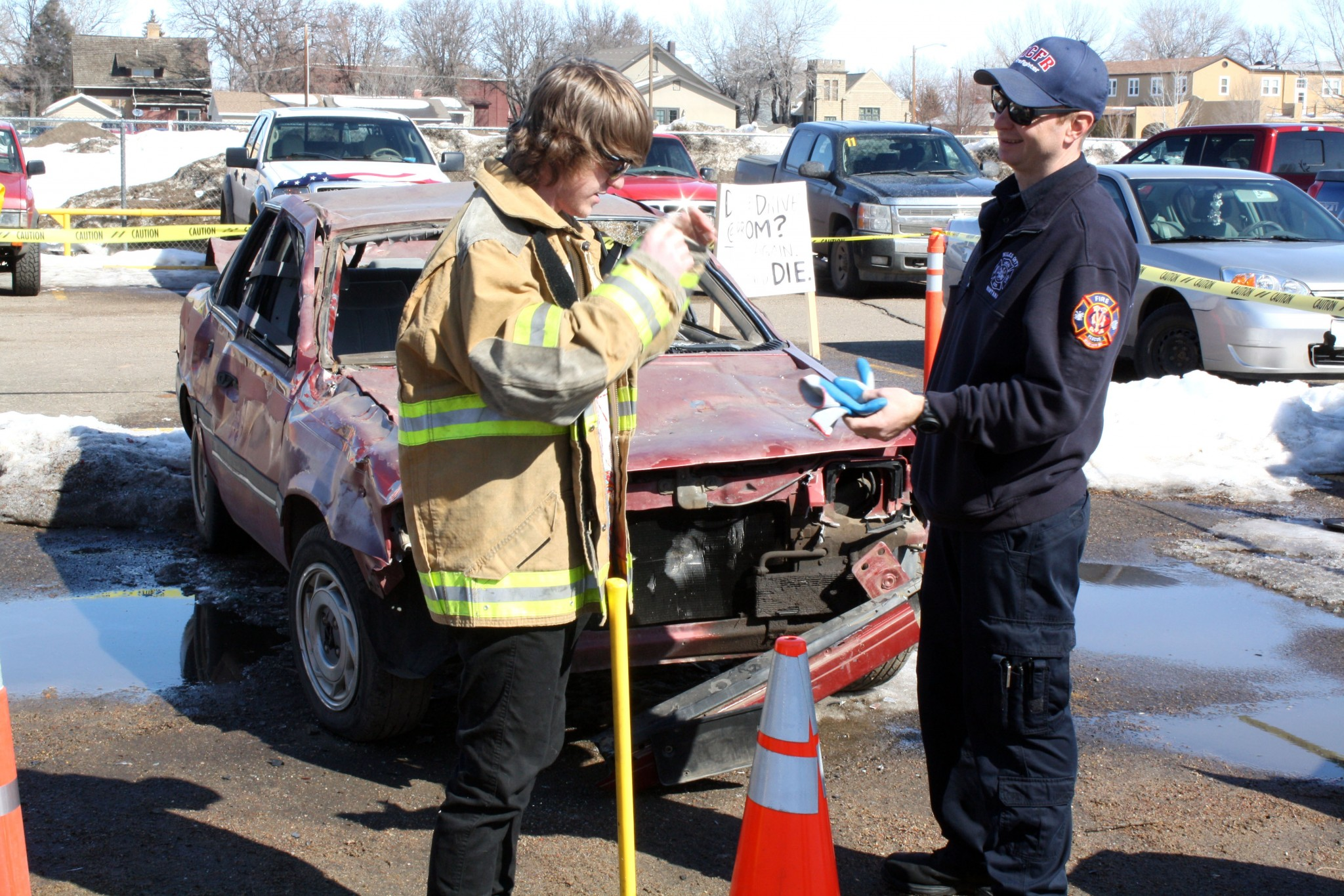 <strong>David Richter, a senior, puts on a pair of safety glasses, a heavy jacket, and a pair of work gloves provided by firefighter Brad Davis before he takes his turn putting a few fresh dents in the sedan provided by Northside Auto Dismantlers. The car was provided free by the yard and will be scrapped when the fire department is done with it. The fire department hopes the exercise will not only get students talking, but thinking about the topic of intoxicated driving. </strong>