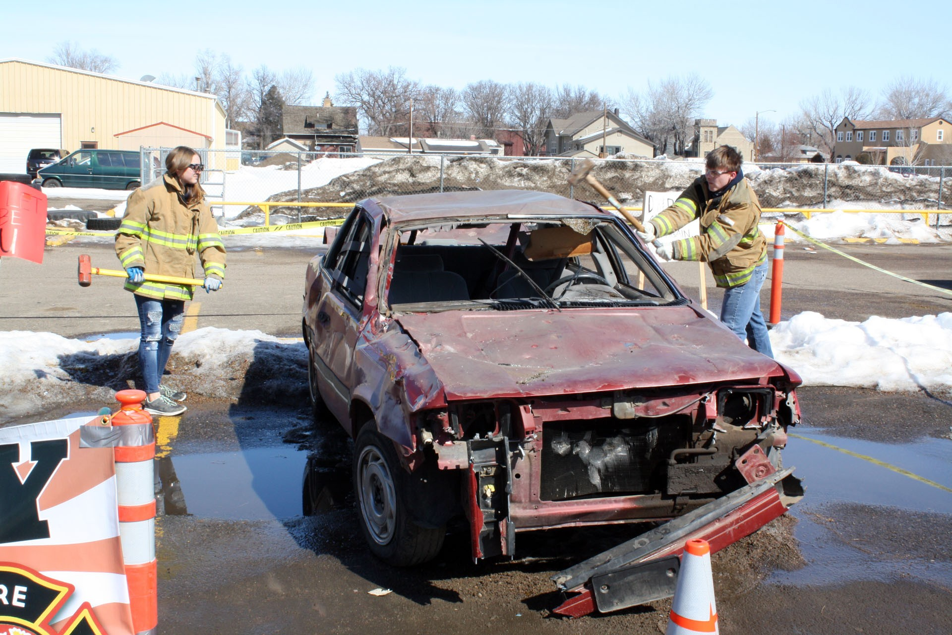 "<strong>Kaitiey Penrod, left, and Tyson Hancock, both Juniors each take a few swings at the car. Miles City Fire and Rescue EMT Adrian Davis hopes their ability to participate in ""wrecking"" the car will reinforce the message their trying to send: don't drive while intoxicated, and don't get in the car with someone who is either.</strong>"