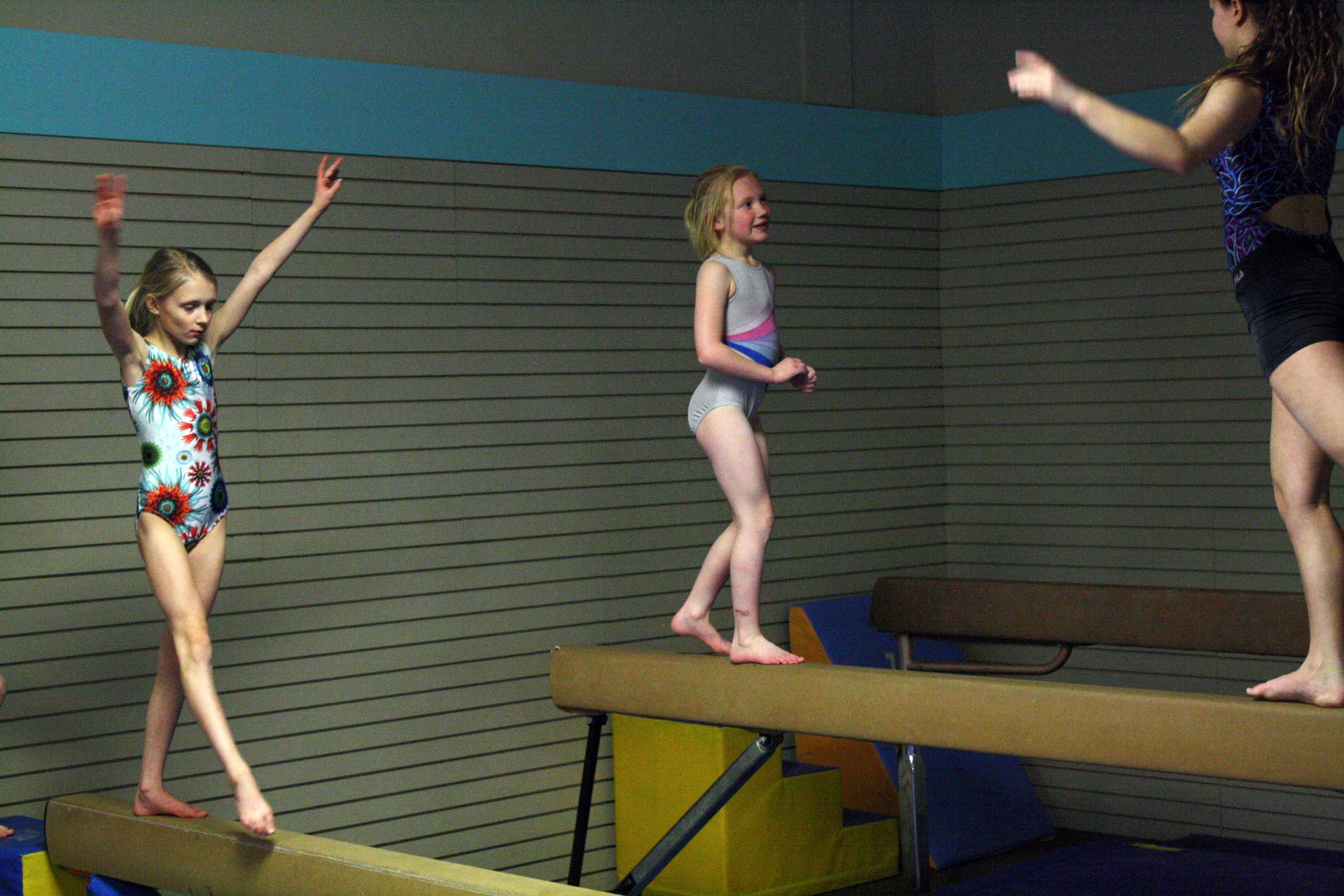 <strong>Gwendolyn Garvin, 8, left, and Allie Shepherd, 7, practice their balance beam skills. Each girl went back and forth multiple times, practicing different elements of their beam routines. Garvin scored 9.1 on her beam routine, which earned her the top spot for her age group. Shepherd scored a 9.25 for her beam routine, earning her a gold medal.</strong>