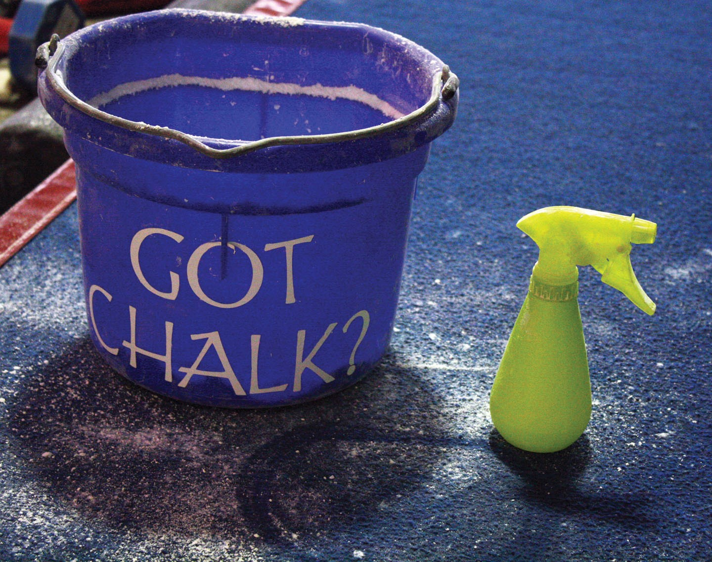 <strong>Next to the uneven bars the gymnasts have a chalk bucket and a small water bottle. They take turns wetting their palms and getting a sufficient layer of chalk to help reduce the chance of their hands slipping.</strong>