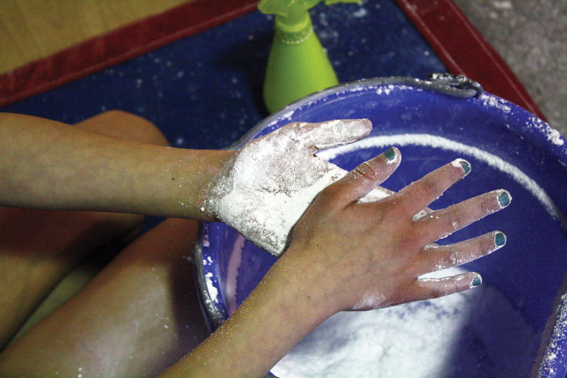 <strong>Gwendolyn Garvin puts chalk on her hands after running through her bars routine once. Each gymnast applies more chalk before every attempt, to help keep her grip consistent.</strong>