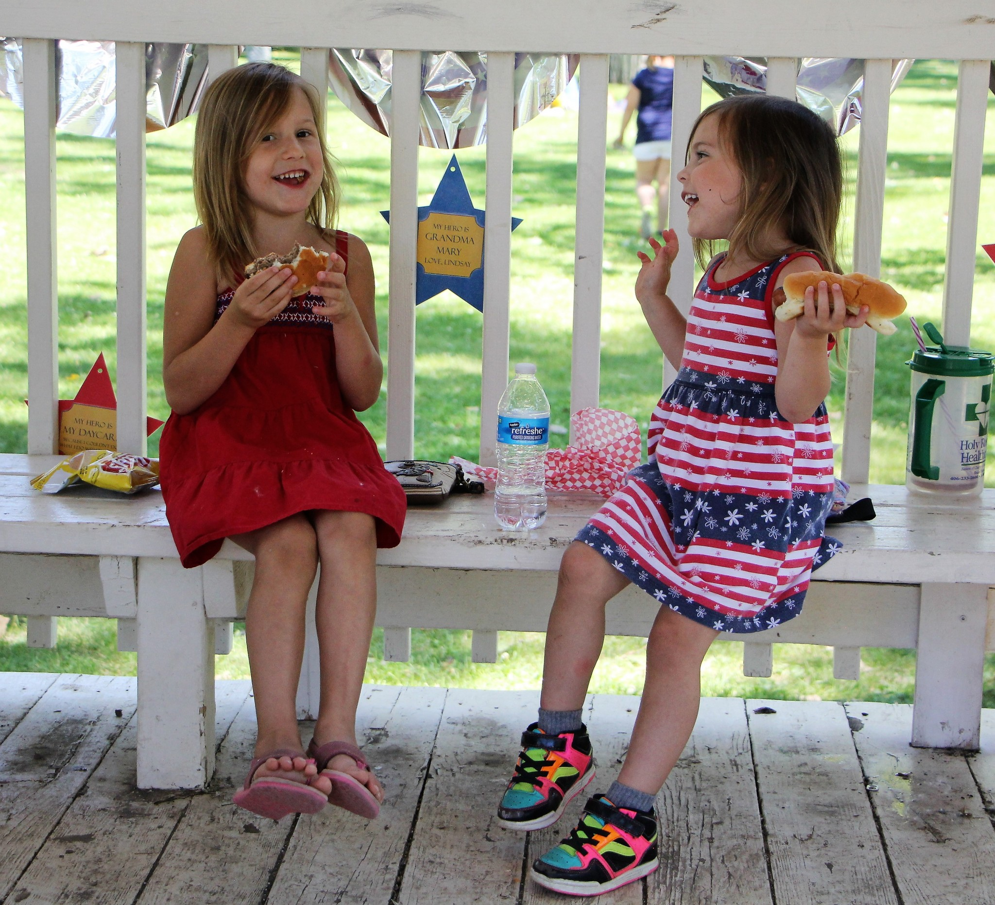 <strong>STAR PHOTOS/Sharon Moore</strong><strong>Melzie Liles, 5, and Tallia Liles, 3, eat lunch from the Wake Up and Lace Up barbeque that was set up in Riverside Park after the 4th of July Parade on Wednesday. Melzie enjoyed a burger while Tallia enjoyed a hot dog.</strong>